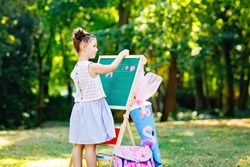 Happy little kid girl standing by big chalk desk. schoolkid on first day of elementary class with satchel and traditional gift cone. Healthy child writing and painting outdoors. Copyspace on desk.
