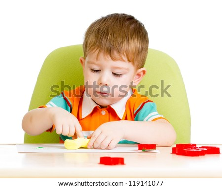 Happy little kid sitting at table and playing with colorful clay toy