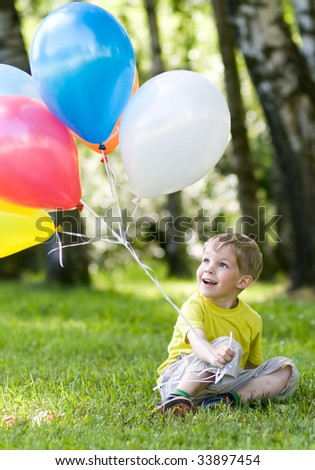 Happy little kid with colorful balloons in summer park