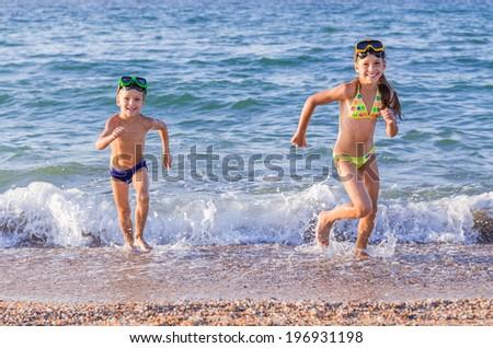 Happy little kids runs from the sea