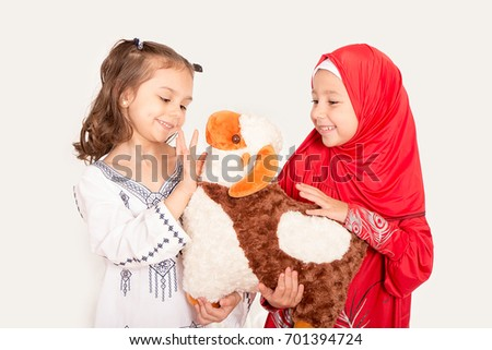 Happy little Muslim girls playing with sheep toy - celebrating Eid ul Adha - Happy Sacrifice Feast #701394724