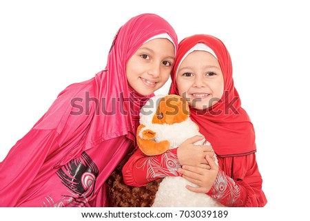 Happy little Muslim girls playing with sheep toy - celebrating Eid ul Adha - Happy Sacrifice Feast #703039189