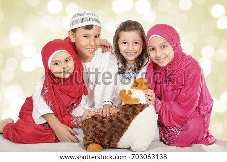 Happy little Muslim kids playing with sheep toy - Family celebrating Eid ul Adha - Happy Sacrifice Feast #703063138