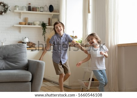 Happy little preschooler siblings have fun run around kitchen together, smiling small brother and sister feel playful racing playing engaged in funny childish activity at home, entertainment concept