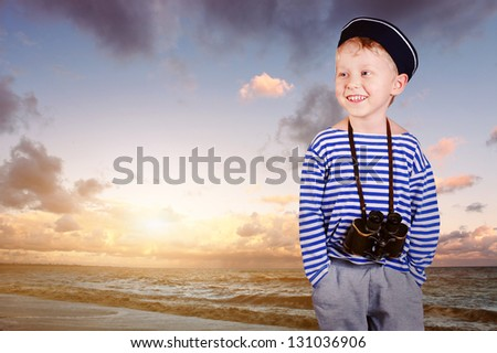 Happy little sailor boy with binoculars at the sea view