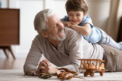 Happy little schoolboy lying on older senior grandfather on floor carpet, having fun together in living room. Joyful different generations family playing, enjoying free weekend time at home.