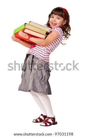 Happy little schoolgirl with a stack of heavy books. Isolated over white