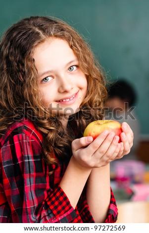 Happy little schoolgirl with apple  - portrait in classroom