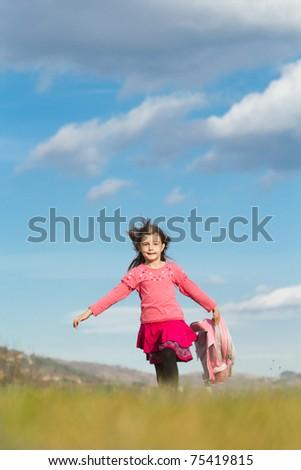 Happy little schoolgirl with bag running on fied