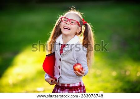 Happy little schoolgirl with lunch, book and pencils. Back to school outdoor