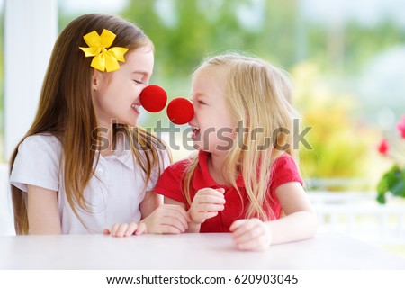 Happy little sisters wearing red clown noses having fun together on sunny summer day at home. Two kid playing together.