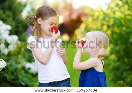 Happy little sisters wearing red clown noses having fun together on sunny summer day outdoors