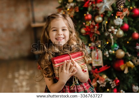 Happy little smiling girl with christmas gift box. #336763727