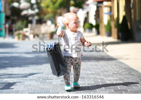 Happy little toddler girl walking on the street in the middle of the