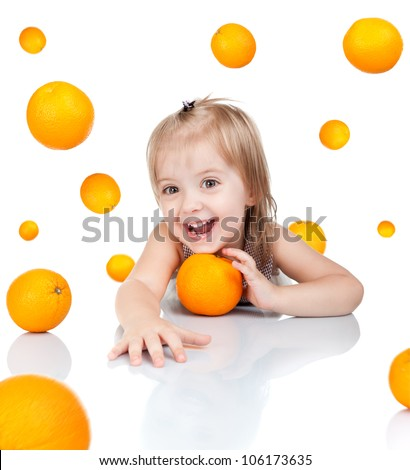 Happy little 2 year girl smile with orange, cute child sitting at table looking at camera oranges fly around isolated over white background, concept of vitamin fruit