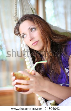 happy long-haired girl drinking lemonade in comfortable cottage