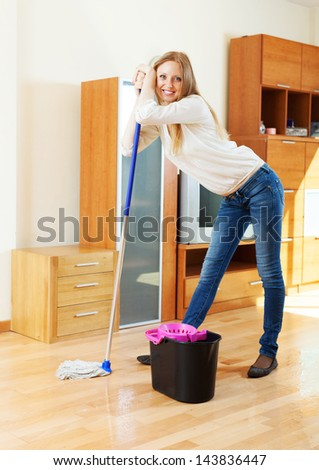 Happy long-haired housewife washing floor with mop