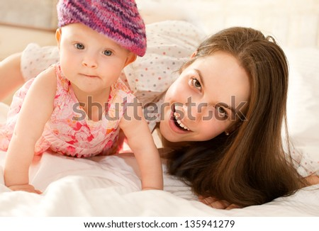 happy-looking baby wearing knitting hat and  beautiful mother playing together on the bed
