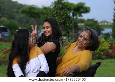 Happy looking Indian mother with her young daughters sitting on a gardens bench. Concept Mother's day