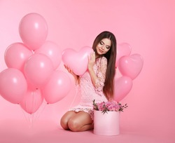 Happy love brunette girl with balloons and bouquet of rose flowers in hat box isolated on pink studio background.