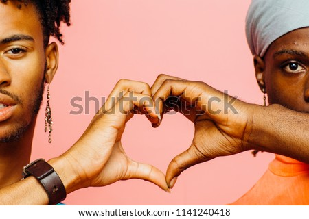 Happy love/ Two men making a heart shape with their hands, isolated on pink studio background Stockfoto ©