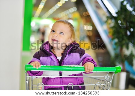 happy lovely baby sitting in shopping trolley