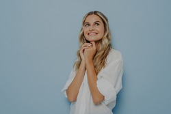 Happy lovely blonde girl feeling nostalgic recalling romantic memories, holding hands together and looking up with smile while standing isolated on blue studio background with copy space