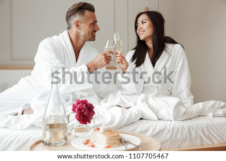 Happy lovely couple caucasian man and asian woman wearing white housecoat smiling to each other and drinking sparkling wine during breakfast in bed at hotel room
