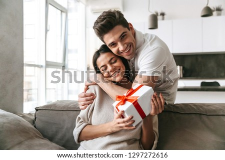 Happy lovely young couple celebrating together while sitting on a couch at home, giving presents
