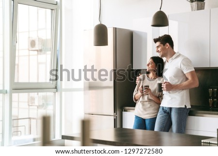 Happy lovely young couple holding cups while standing at the kitchen at home, looking at the window