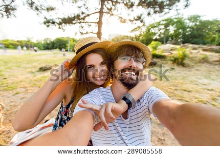 Happy lovers, attractive woman and man walking in park  enjoying romance.   funny couple making selfie, smiling and have fun together.