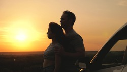 Happy lovers travel by car. A man and a woman hug near the car and admire beautiful sunset at campsite. Tourists travel by car, admire sunrise, nature. Free travelers, tourists. Family travel by car.