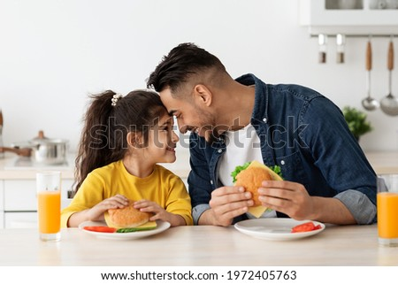 Happy Loving Arab Dad And Daughter Eating Sandwiches In Kitchen And Bonding, Cheerful Middle Eastern Father And Cute Little Female Child Touching Foreheads And Smiling, Enjoying Time Together