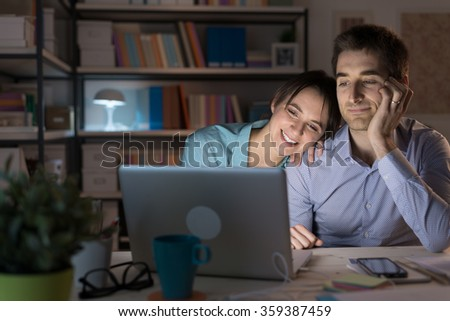 Happy loving couple at home, sitting at desk and using a laptop they are watching videos online and networking, she is leaning on her husband's shoulder stock photo