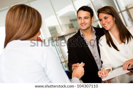 Happy loving couple checking in at a hotel
