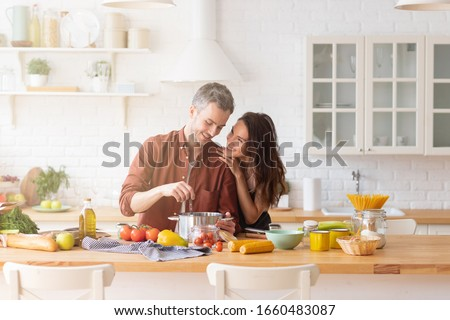Happy loving couple cooking dinner together on kitchen. Young married man and woman preparing fresh organic vegetable. Husband surprising wife with culinary skill. Trendy loft home interior