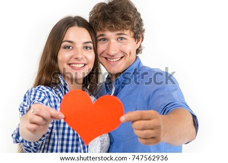 Happy loving couple. Enamored couple of young people. Man and woman holding in their hands red hearts. Symbol of love. Valentine's Day. #747562936