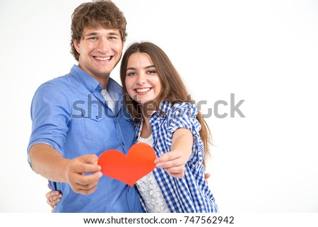 Happy loving couple. Enamored couple of young people. Man and woman holding in their hands red hearts. Symbol of love. Valentine's Day. #747562942