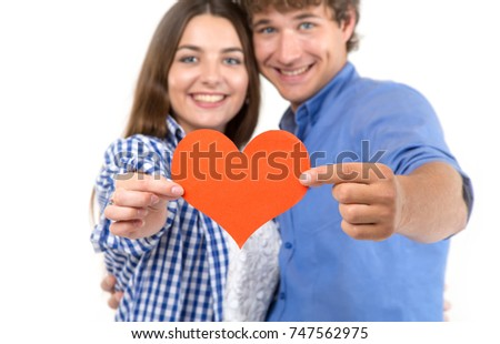 Happy loving couple. Enamored couple of young people. Man and woman holding in their hands red hearts. Symbol of love. Valentine's Day. #747562975