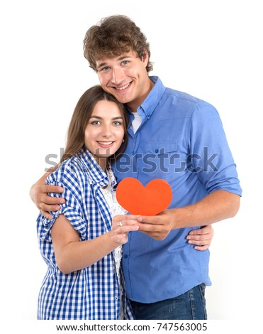 Happy loving couple. Enamored couple of young people. Portraits man and woman holding in their hands red hearts. Symbol of love. Valentine's Day. #747563005