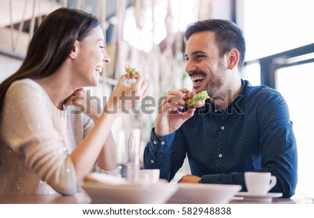Photo of  Happy loving couple enjoying breakfast in a cafe. Love, dating, food, lifestyle
