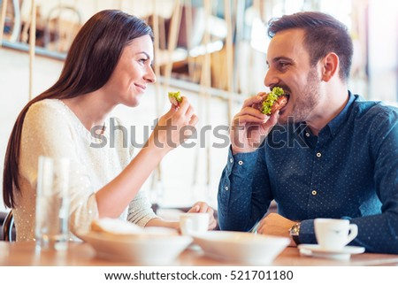 Happy loving couple enjoying breakfast in cafe. Love, food and  lifestyle concept. #521701180