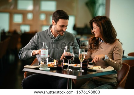 Happy loving couple enjoying in restaurant. Young couple enjoying in food.