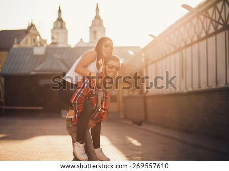 Happy loving couple. funny young man piggybacking his girlfriend. sunset