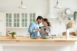 Happy loving couple holding wine glasses, touching foreheads, enjoying tender moment, romantic date, standing in modern kitchen at home together, smiling wife and husband celebrating anniversary