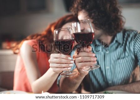 Happy loving couple is bonding to each other with fondness. Focus on glasses of red wine in their hands  #1109717309
