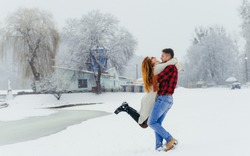 Happy loving couple is having fun in the winter forest. The man is spinning round his beautiful red head woman during the snowfall.