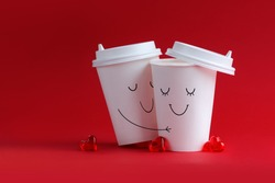 Happy loving couple of emoticons drawn on coffee cups hugging on a red background. Place for text.