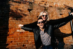 happy loving couple on a brick wall background. portrait of a man and a woman of European appearance laughing, holding hands, arms to the sides, depicting flight. High quality photo