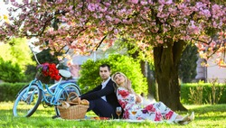 Happy loving couple relaxing in park with food. Romantic picnic with wine. Give uncommon, unique gifts spontaneously. Enjoying their perfect date. Couple in love picnic date. Spring weekend.